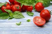 Fresh tomatoes with basil on wooden table close up — Stock Photo