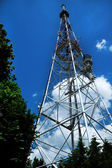 Telecommunication tower over blue cloudy sky — Stock Photo