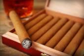 Cigarrer och bränna en med cognac på träbord, närbild — Stockfoto