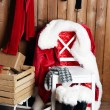 Santa costume hanging on wooden wall — Stock Photo #79708474