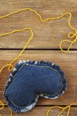 Denim heart and thread on wooden background — Stock Photo