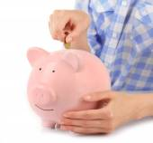 Hands putting coin into pink piggy bank — Stock Photo
