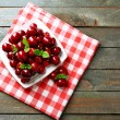Sweet cherries with green leaves on plate, on wooden background — Stock Photo #80066600