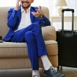 Business man with suitcase sitting on sofa at home — Stock Photo #80208082