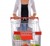 Young woman with shopping cart isolated on white — Stock Photo