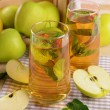 Glasses of apple juice with fruits and fresh mint on table close up — Stock Photo #80211530
