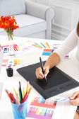 Artist drawing on graphic tablet in office — Stock Photo
