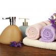 Soft towels with dispenser and flowers — Stock Photo #80285154
