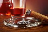 Cigarrer och bränd med aska och cognac på träbord, närbild — Stockfoto
