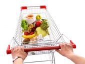 Young man with shopping cart isolated on white — Stock Photo