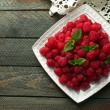 Sweet raspberries on plate on wooden  background — Stock Photo #80824802