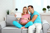 Young pregnant woman with husband on sofa in room — Stock Photo