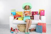 Femme avec des sacs et des chaussures sur le canapé dans la chambre — Photo