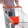 Young man with empty shopping cart isolated on white — Stock Photo #80890724