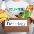 Volunteer holding donation box with food — Stock Photo #80894364