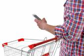 Young man holding mobile phone and shopping cart isolated on white — Stock Photo