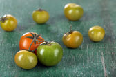 Green tomatoes on wooden table — Stock Photo