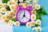 Small alarm clock with beautiful flowers — Stock Photo