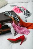 Suitcase with clothing on bed — Stock Photo