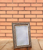 Photo frame standing on table on brick wall background — Stock Photo