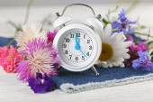 Small alarm clock with beautiful flowers on table close up — Stock Photo