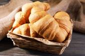 Delicious croissants in wicker basket on table close-up — Stock Photo