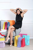 Belle jeune femme avec des sacs à provisions et boîtes assis sur le canapé dans la chambre — Photo