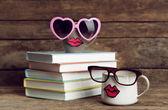 Vintage boeken en cups met lippen op houten achtergrond — Stockfoto