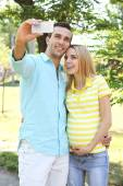 Young pregnant woman with husband making selfie in park — Stock Photo