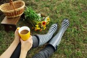 Woman with cup sitting on meadow — Stock Photo