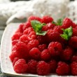 Sweet raspberries on plate on wooden  background — Stock Photo #81521162