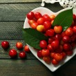 Sweet cherries with green leaves on plate, on wooden background — Stock Photo #81521166
