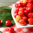 Sweet cherries with green leaves on plate, on wooden background — Stock Photo #81521172