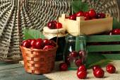 Sweet cherries with green leaves  in basket and wooden boxes, on wooden background — Stock Photo