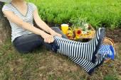 Jonge vrouw in rubber laarzen zittend op de weide buitenshuis — Stockfoto