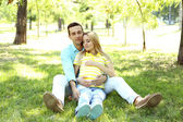 Young pregnant woman with husband sitting on green grass in park — Stock Photo