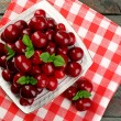 Sweet cherries with green leaves on plate, on wooden background — Stock Photo #81936726