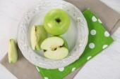 Groene appels in plaat op tafel met servet, close-up — Stockfoto