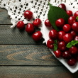 Sweet cherries with green leaves on plate, on wooden background — Stock Photo #82092414
