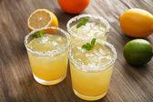 Glasses of lemon juice on wooden table, closeup — Stock Photo