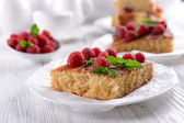 Fresh pie with raspberry in saucer on wooden table, closeup — Stock Photo