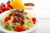 Spaghetti Bolognese on white plate, on color wooden background — Stock Photo