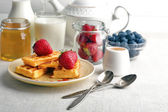 Sweet homemade waffles with forest berries and sauce on table background — Stock Photo