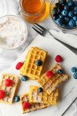 Sweet homemade waffles on tray, on light background — Stock Photo