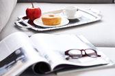 Lekkie śniadanie i magazynów na kanapie w salonie, z bliska — Zdjęcie stockowe