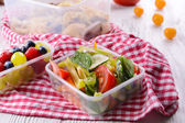 Tasty lunch in plastic containers on wooden table close up — Stock Photo