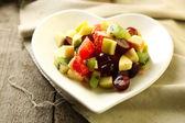 Salade de fruits sur la plaque, sur fond de bois — Photo