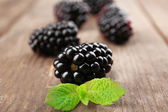 Ripe blackberries with green leaves on wooden background — Stock Photo