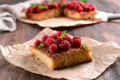 Fresh pie with raspberry on parchment on wooden table, closeup — Stock Photo