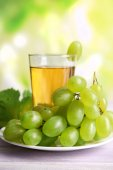Glass of grape juice on wooden table on light blurred background — Stock Photo